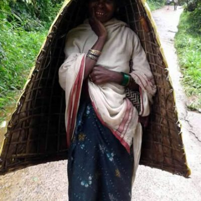 An old tribe woman wearing a traditional natural umbrella
